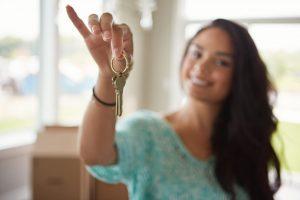 Focus sur clé tenue par femme floue